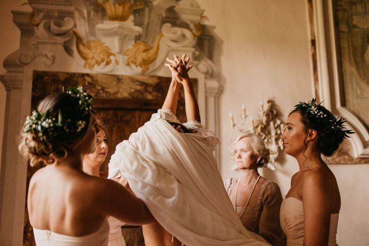 Wedding Morning Bridal Preparations with Bridesmaids Helping Bride into Her Wedding Dress