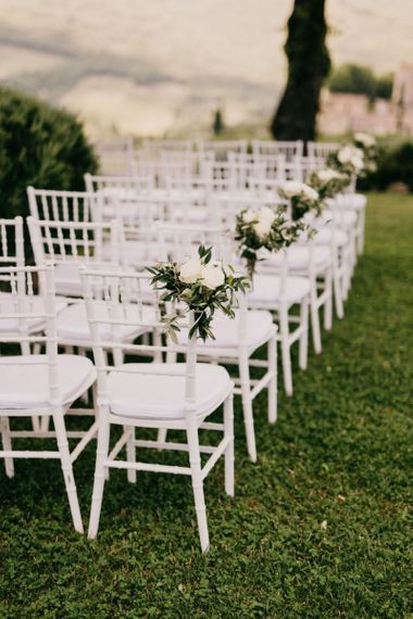 White Ceremony Chairs with Floral Chair Decor