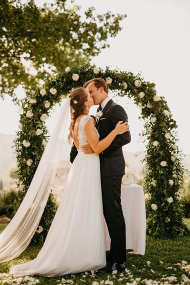 Bride in Bespoke Wedding Dress and Groom in Tuxedo Kissing at the Wedding Ceremony
