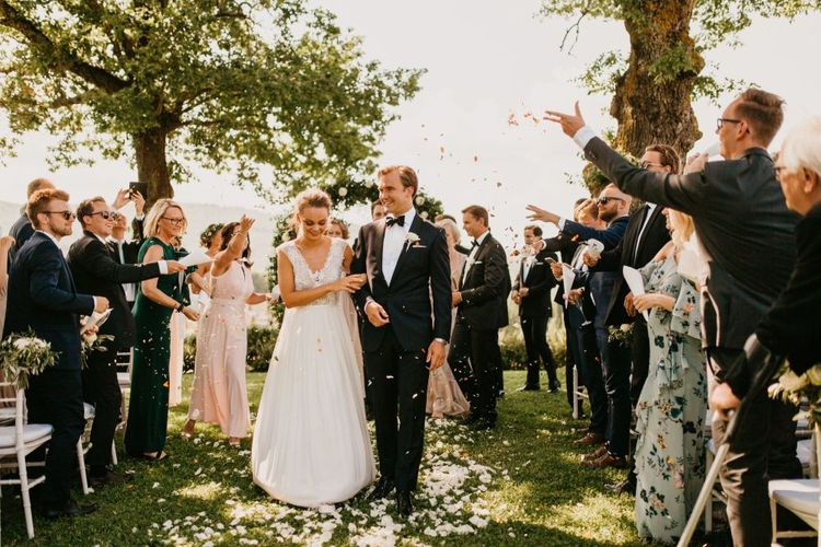 Confetti Moment with Bride in Bespoke Wedding Dress and Groom in Black Tie Suit Walking Up The Aisle