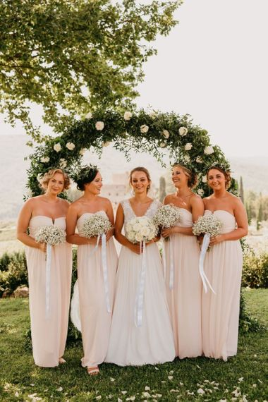 Bridal Party Portrait in Front of a White and Green Floral Arch