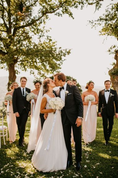 Bride and Groom Kissing in Front of of their Wedding Party