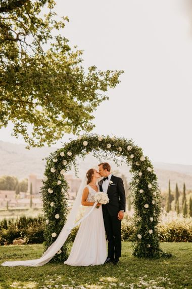 Bride in Bespoke Wedding Dress and Groom in Tuxedo Kissing in Front of White and Green Floral Arch