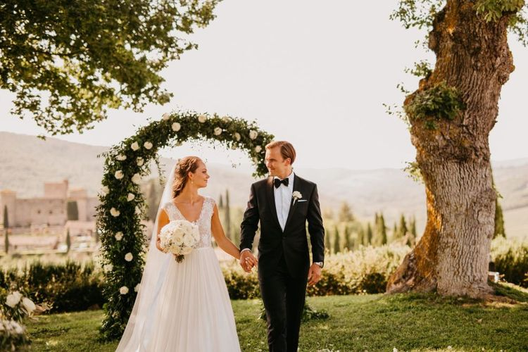 Bride in Bespoke Wedding Dress and Groom in Tuxedo Holding Hands in Front of White and Green Floral Arch