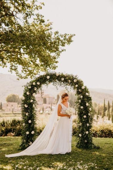 Bride in Bespoke Wedding Dress Standing in Front of White and Green Floral Arch