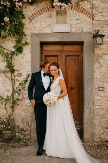 Bride in Bespoke Wedding Dress with Pure White Bouquet and Groom in Black Tie Suit