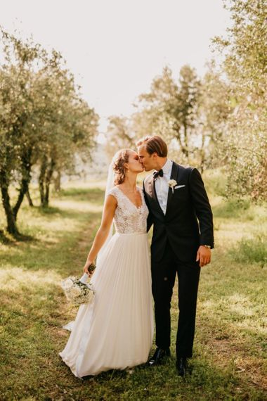 Bride in Bespoke Wedding Dress with Lace Bodice and Groom in Tuxedo Kissing