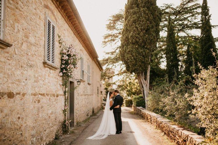 Bride in Bespoke Wedding Dress and Groom in Black Tie Suit Posing Next to Their Italian Castle Wedding Venue