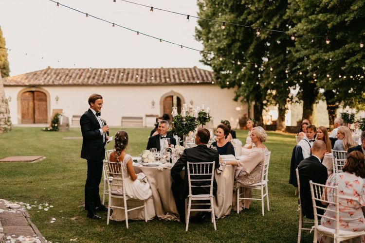 Groom in Tuxedo and Bow Tie Giving His Wedding Speech at The Outdoor Wedding Reception
