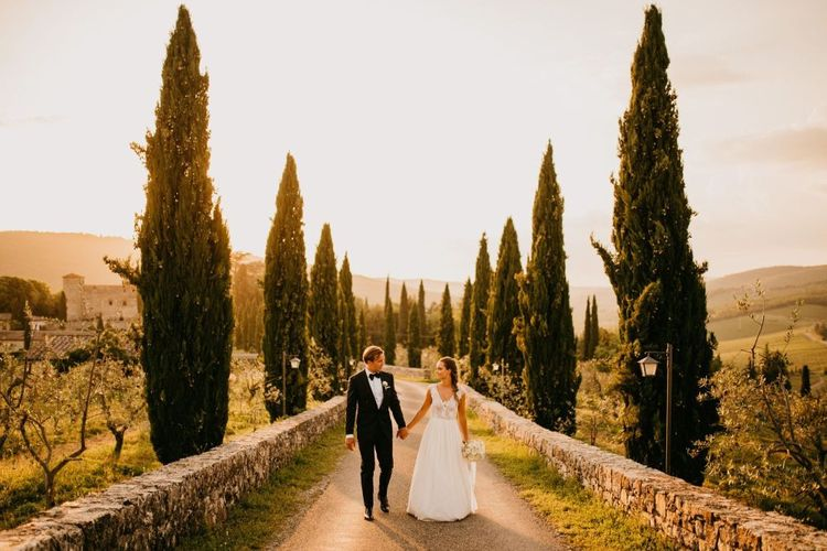 Golden Hour Portrait with Bride in Bespoke Wedding Dress and Groom in Tuxedo and Bow Tie Holding Hands