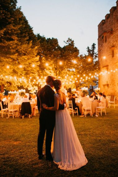 Bride and Groom Embracing at Their Outdoor Italian Castle Wedding Reception