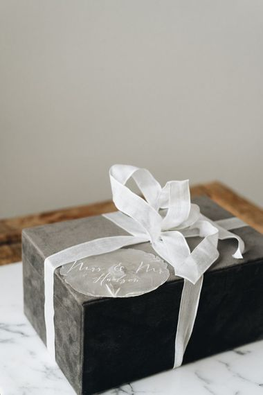 Grey Gift Box Tied with White Ribbon and Clear Gift Tag