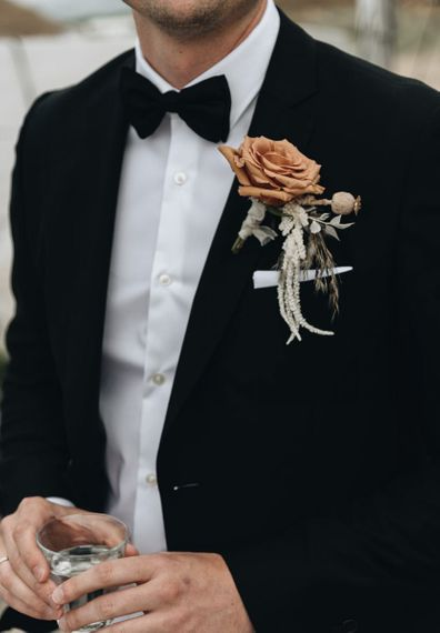 Groom in Tuxedo with Muted Orange Buttonhole