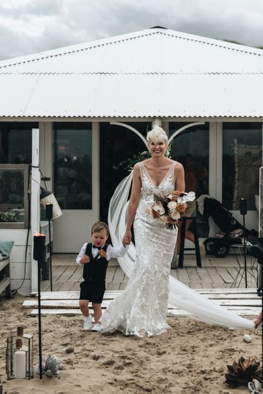 Bride with Short Hair in Made with Love Wedding Dress Walking Down the Aisle with Her Son