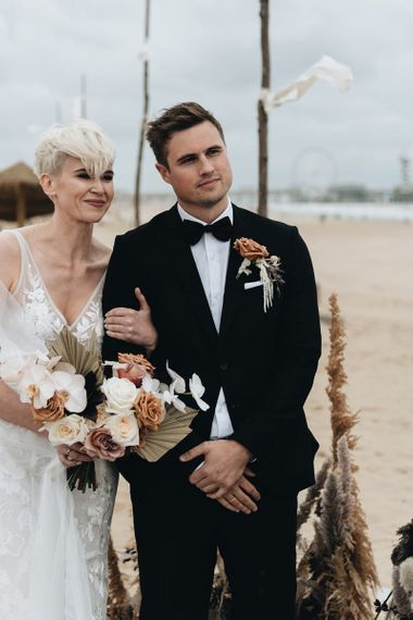 Bride with Short Hair in Made With Love Wedding Dress and Groom in Tuxedo at Beach Wedding Ceremony