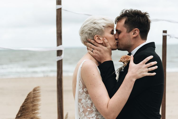 Bride and Groom Kissing During the Beach Wedding Ceremony
