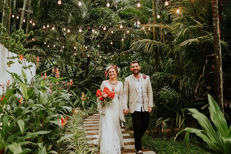 Bride and Groom Amongst Palm Trees and Pontoon Lighting
