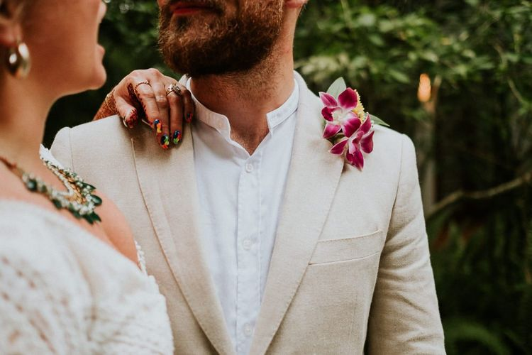 Groom Wearing Cream Jacket And Pink Floral Buttonhole