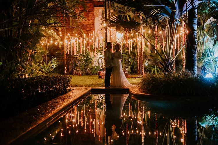 Tropical Plants Lit Up Poolside With Bride and Groom