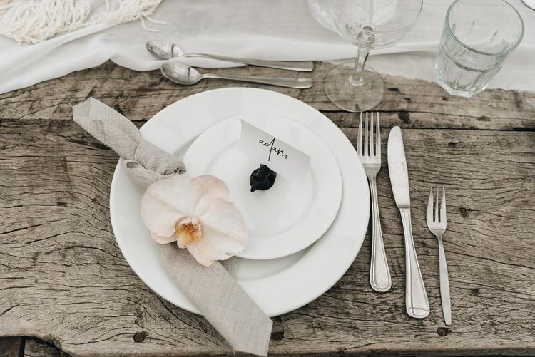 Place Setting with White Place, Linen Napkin and Orchid