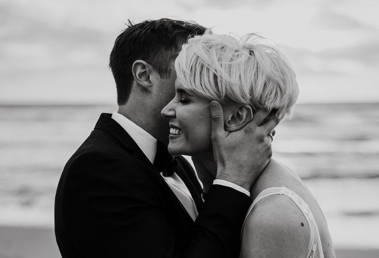 Black and White Portrait of Groom Kissing His Bride with Short Hair