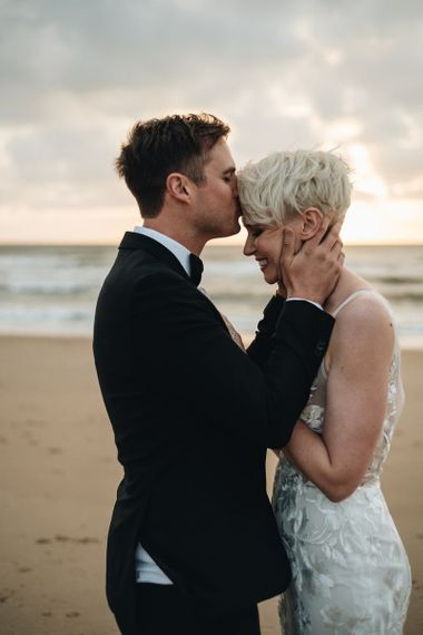 Groom in Tuxedo Kissing His Brides Forehead on the Beach