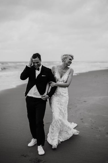 Portrait of Bride and Groom Walking Along the Beach