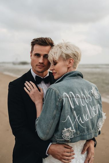 Groom in Tuxedo and Bride in Personalised Denim Jacket Embracing