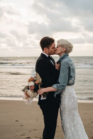 Groom in Black Tie Suit Kissing Kiss Bride in a Denim Jacket on the Beach