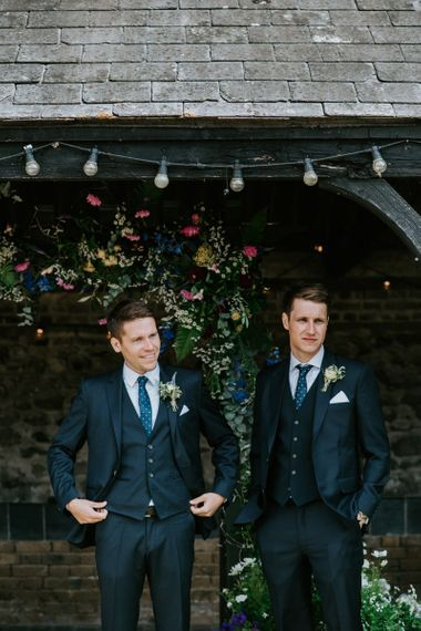 Groomsmen in Navy Hugo Boss Wedding Suits at Floral Covered Arbour