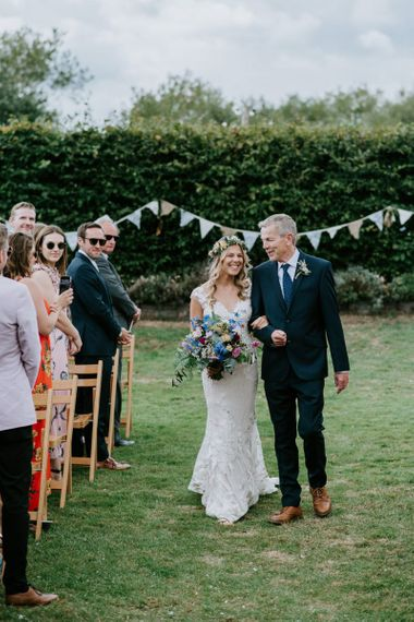 Outdoor Wedding Ceremony Bridal Entrance in Lace Watters Wedding Dress and Colourful Flower Crown and Wedding Bouquet