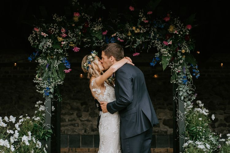 Bride in Lace Watters Wedding Dress and Groom in Navy Hugo Boss Suit Kissing at the Flower Covered Altar