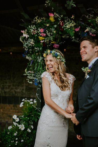 Bride in Lace Watters Wedding Dress and Groom in Navy Hugo Boss Suit Holding Hands Laughing at the Flower Covered Altar