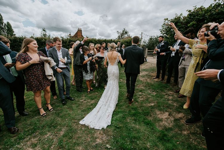 Confetti Moment with Bride in Lace Watters Wedding Dress and Groom in Navy Hugo Boss Suit