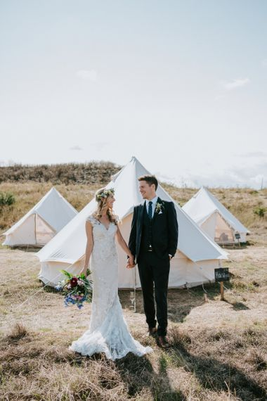 Bride in Lace Watters Wedding Dress and Groom in Hugo Boss Suit Standing in their Glamping Field