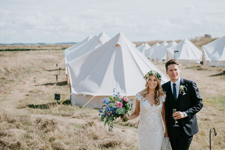 Bride in Lace Watters Wedding Dress and Groom in Hugo Boss Suit Standing in Front of Bell Tent