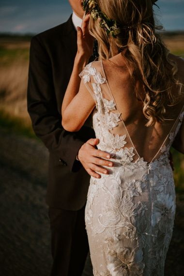 Groom Embracing His Bride in a Lace Watters Wedding Dress