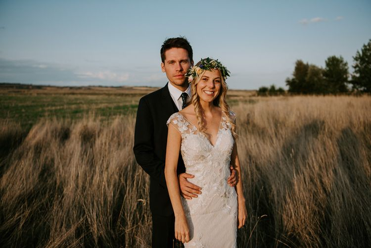 Groom in Hugo Boss Suit and Bride in Lace Watters Wedding Dress Standing in a Field
