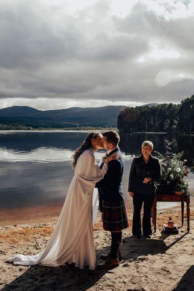 Bride in Vintage Wedding Dress with Bell Sleeves and Groom in Tartan Kilt Kissing at Outdoor Wedding Ceremony at Loch Garten in Scotland