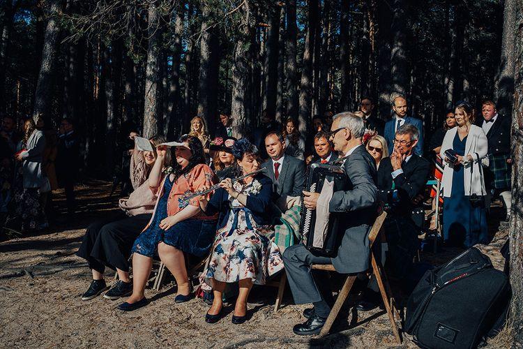 Wedding Guests Playing Music at Outdoor Wedding Ceremony at Loch Garten in Scotland