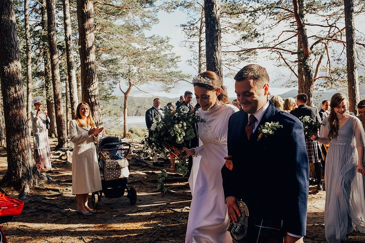 Bride in High Neck Vintage Wedding Dress and Groom in Traditional Scottish Highland Wear Exiting the Wedding Ceremony