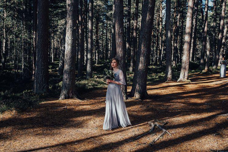 Bridesmaid Walking Down the Woodland Aisle in a Blue BHLDN Dress