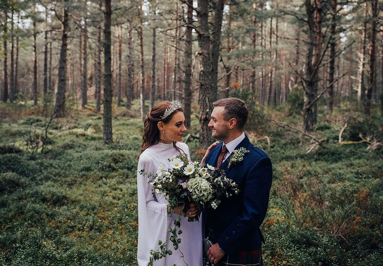 Bride in Vintage Wedding Dress with High Neck and Crown and Groom in Traditional Tartan Kilt Highland Wear