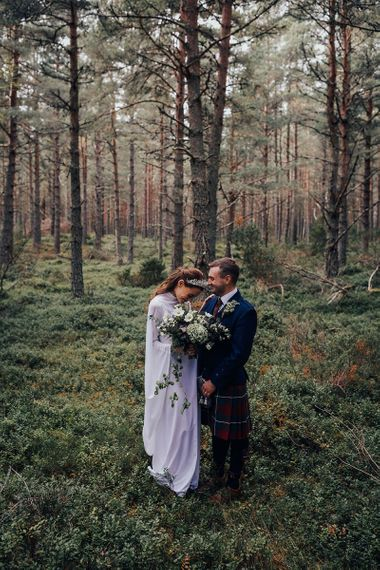 Bride in Vintage Wedding Dress with High Neck and Crown and Groom in Traditional Tartan Kilt Highland Wear in the Woodland