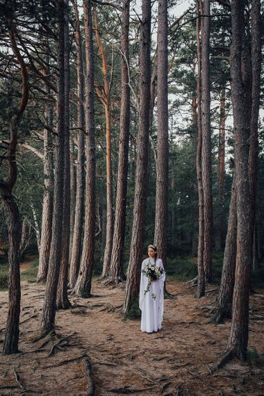 Bride in Vintage Wedding Dress and Crown Standing in the Woods