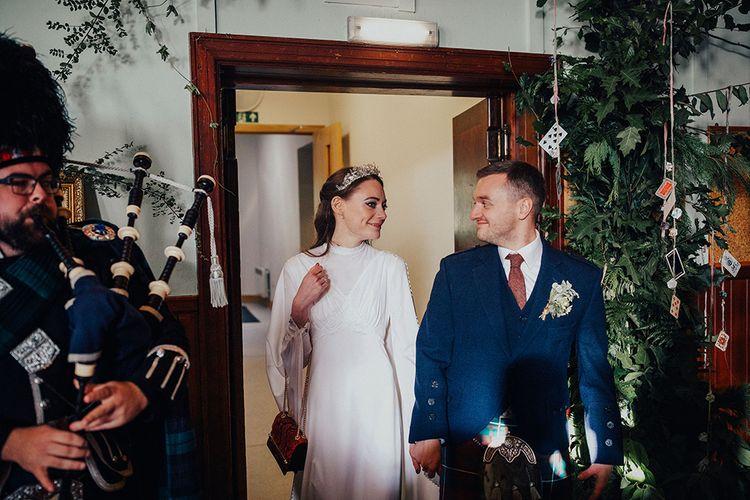 Bride in High Neck Vintage Wedding Dress and Groom in Scottish Highland Wear Entering their Village Hall Wedding Reception
