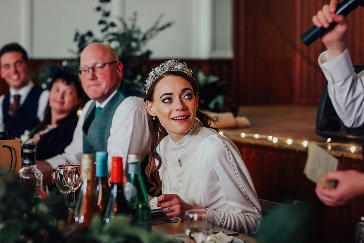 Bride in High Neck Vintage Wedding Dress and Crown Smiling During Grooms Wedding Speech