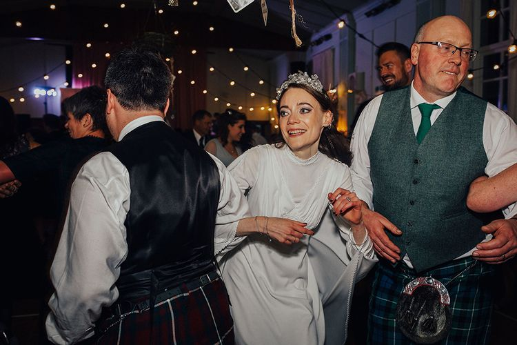 Bride in Vintage Wedding Dress and Wedding Guests Dancing to a Ceilidh Band