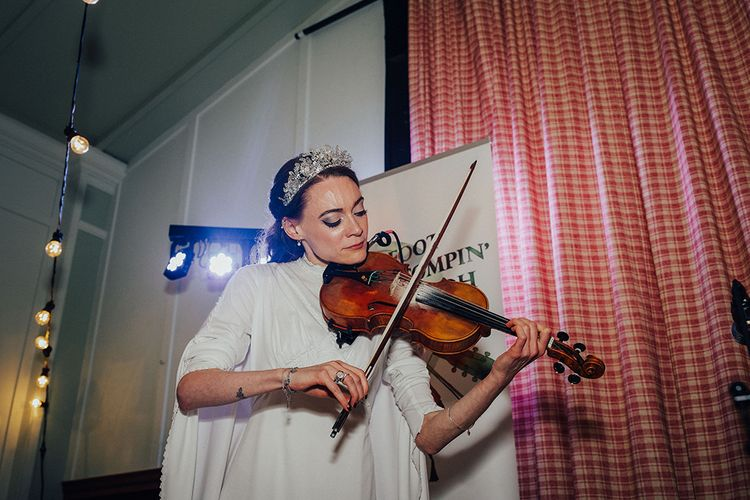 Bride in Vintage Wedding Dress with High Neck Playing a Violin