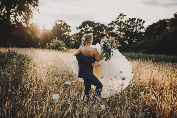 Groom Carries Bride Through Field For Summer Wedding